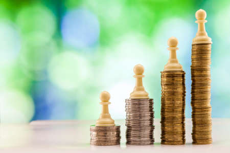 Growing coins stacks with green and blue sparkling bokeh background. Chess figures standing on coins meaning power and career growth. Financial growth, saving money, business finance wealth and success concept. Stock Photo