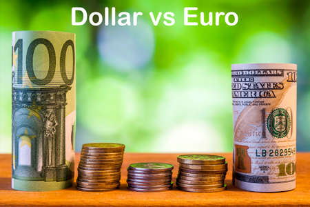 One hundred euro and one hundred US dollar rolled bills banknotes, with euro coins and american cents on green blurred bokeh background. Dollar vs Euro concept. Stock Photo