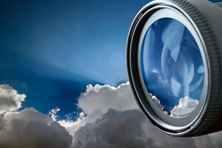 Blue sky with puffy white clouds in bright clear sunny day in digital photo camera lens reflection. Professional Photography Equipment, Photographer Work Kit.