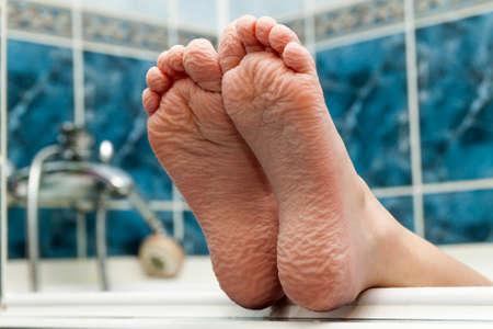 Gerimpelde blote voeten komen uit een badkuip. Jongere die een badvoetenclose-up binnen in badkamers interrior foto krijgen