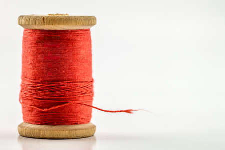 Reel or spool of red sewing thread isolated on white. Shallow depth of field. Close-up macro shot. Stockfoto
