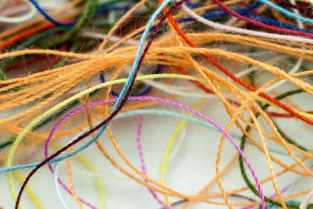 Multi-colored tangled colorful needlecraft silk thread rope. Macro shot. Abstract colors background Stock Photo