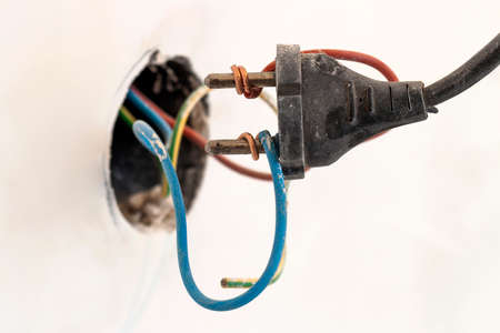 Badly wired plug showing bad and wrong and dangerous connection Фото со стока