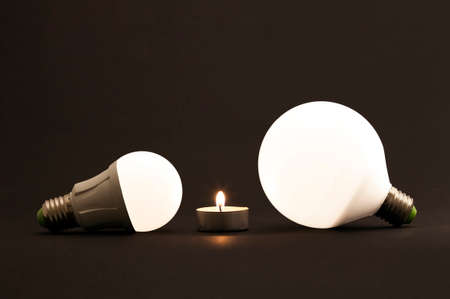 led lighting: White little candle and LED electric bulbs on dark background. Concept describing the evolution of lighting and energy saving.