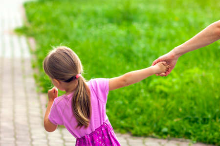 niños saliendo de la escuela: Little girl holding a hand of her mother. Family relations concept.