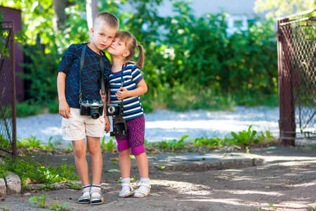 Little boy and a little girl wit two vintage cameras standing together holding hands Stock Photo