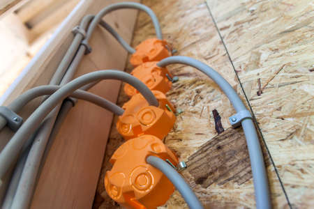 wall socket: New electrical installation, socket plastic boxes and electrical cables on the wall, renovation concept. Electrical wiring installation. Stock Photo
