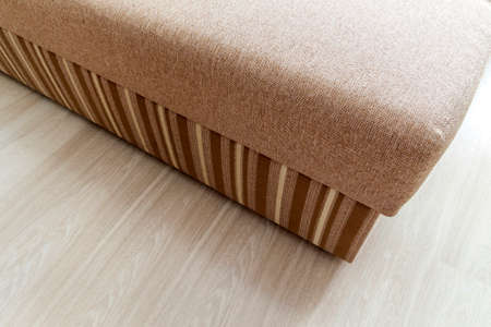 rug texture: Detail of a modern beige textured sofa in living room on wooden laminate parquet floor