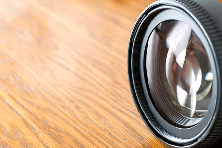 Professional Photography Equipment, Photographer Work Kit. Close-up macro shot of photo camera objective lens on wooden table. Shallow DOF