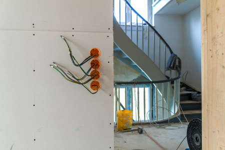 New electrical installation, socket plastic boxes and electrical cables on the wall, renovation concept. Electrical wiring installation. Stock Photo