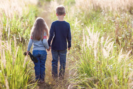 horizont: Little boy and little girl standing holding hands looking on horizont. Rear view.