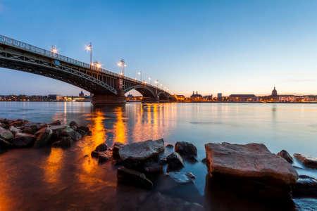 Mooie zonsondergang over de rivier van Rijn  van Rijn en de oude brug in Mainz dichtbij Frankfurt-am-Main, Duitsland.