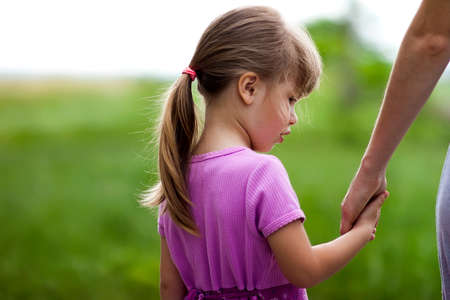 小さな女の子は彼女の母の手を握り.家族関係の概念。