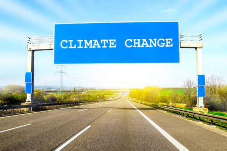 Blue freeway sign over the road on sunny day with words Climate Change on it Stock Photo