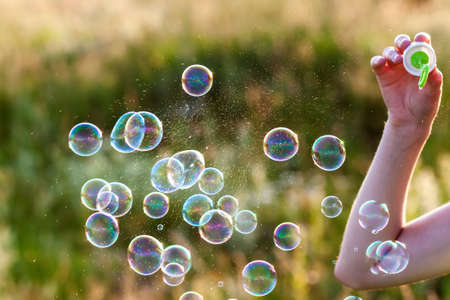 Womans hand with blowing colorful soap bubbles at sunset. Stock Photo