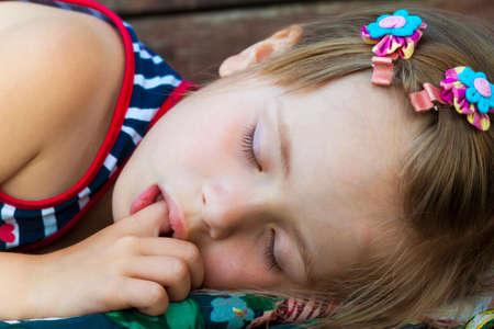 小さなかわいい女の子寝て、親指を吸うと甘い夢を持って