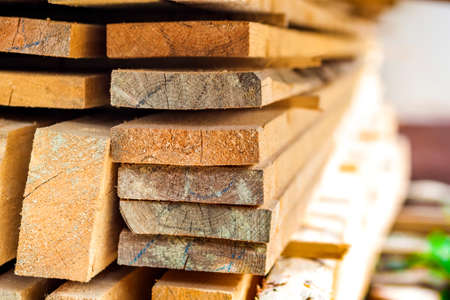 Stack of building lumber at construction site with narrow depth of field. Timber wooden bars.