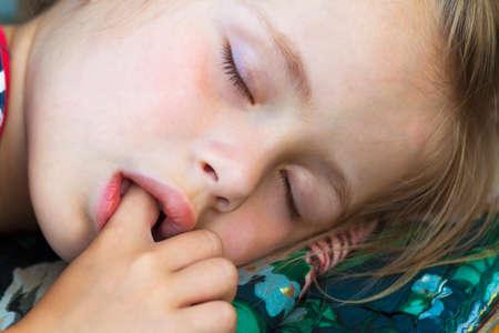 Weinig mooi meisje slapen, zuigen duim en hebben zoete dromen
