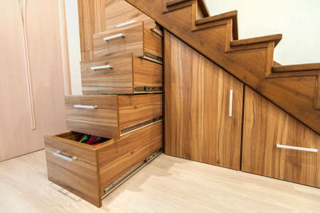 Modern architecture interior with  luxury hallway with glossy wooden stairs in modern storey house. Custom built pullout cabinets on glides in slots under stairs Standard-Bild