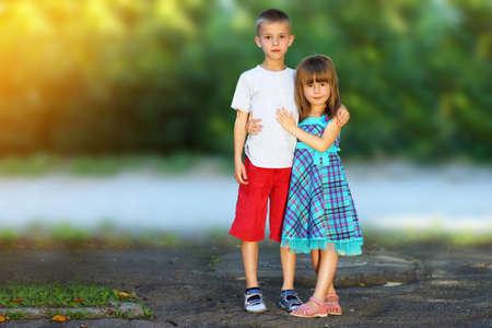 Twee kleine kinderen broer en zus samen. Meisje in jurk knuffelende jongen. Familie relatie concept.