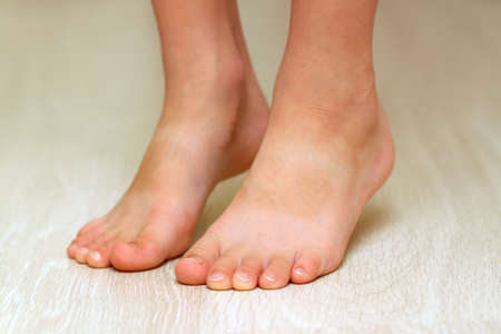 寄木細工の床の子供の足は積層木製テクスチャ床クローズ アップです。ヘルスケアの概念
