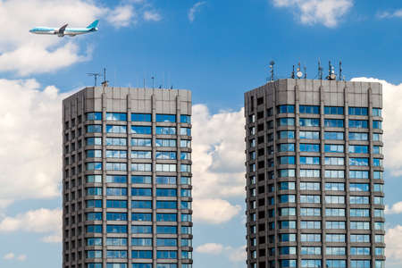 Modern glass and concrete skyscrapers and a plane in the sky Stock Photo