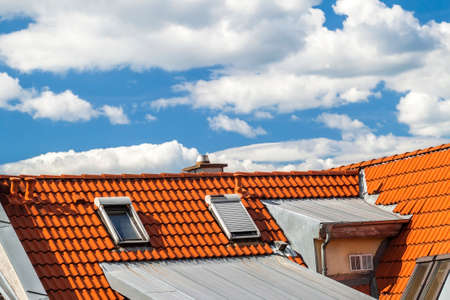 Roof of house with windows and yellow roof tiles