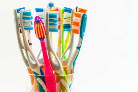 Schließen Sie herauf Schuss des Satzes mehrfarbiger Zahnbürsten im Glas auf sauberer Toilette auf weißem Hintergrund, zahnmedizinisches Konzept.