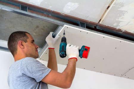 El trabajador de la construcción monta un techo suspendido con paneles de yeso y fija los paneles de yeso al marco de metal del techo con un destornillador.