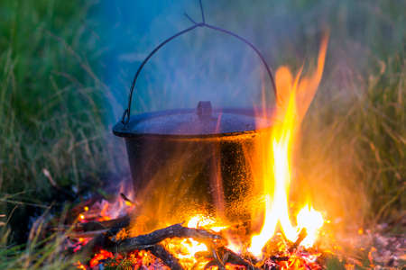 Camping kitchenware - pot on the fire at an outdoor campsite Stock Photo
