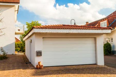 주황색 벽돌 기와 지붕이있는 흰색 차고가 분리되었습니다. 스톡 콘텐츠