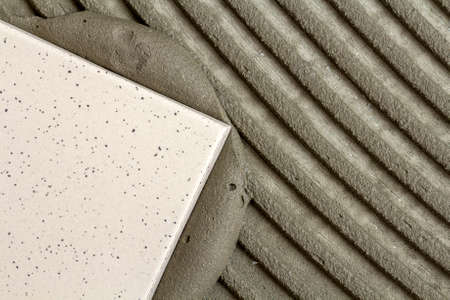 Close-up detail of floor tiles installation. Home improvement, renovation - ceramic tile floor adhesive, mortar.