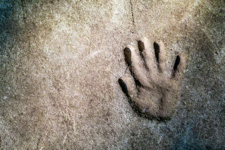 Memorable handprint of a hand in an old concrete wall Stock Photo