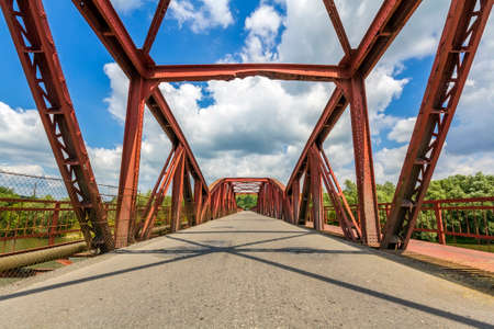 Interior of metal structure of a bridge in sunny day. Perspective to infinity at the bridge in Ukraine