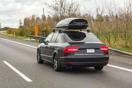 Auto met de containerdoos van de dakbagage voor reis op een weg