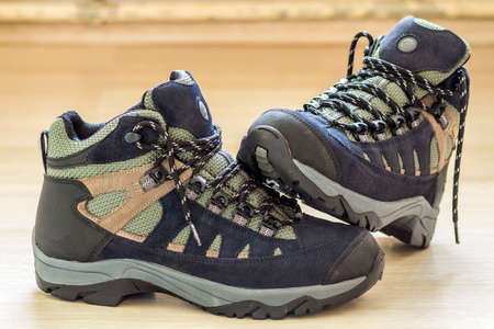 New fashionable hiking mountain boots. Modern leather trekking footware.