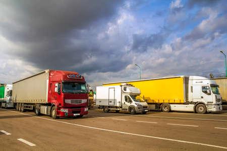 Kleurrijke moderne grote semi-vrachtwagens en aanhangwagens van verschillende merken en modellen staan in rij op een vlakke parkeerplaats van truck stop in de zon