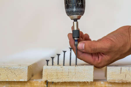 Hand of a worker screws a screw in a wooden board with a cordless screwdriver. Man carpenter at handmade work