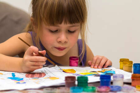 Cute little girl painting with brush and colourful paints