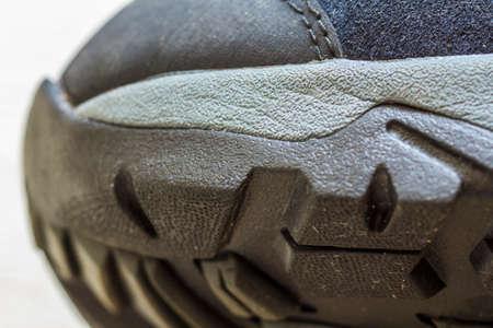 Detail shot of fragmrnt of new fashionable hiking mountain boot. Modern leather trekking footware.