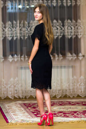 Portrait of beautiful young girl with long hair in black dress and red high heel shoes.