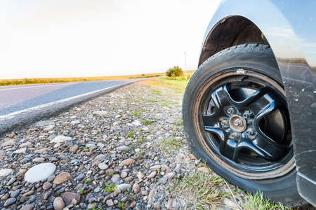 Close up of flat tire on a car on gravel road.
