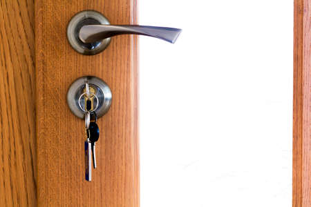 Modern, contemporary satin metal handle and a key in lock on a wooden door close-up.