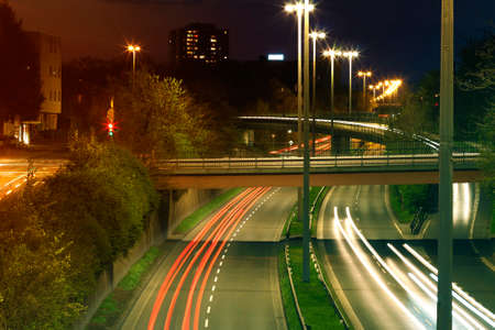 Freeway with urban night traffic with focusing on the road. Car trails on a highway Stock Photo