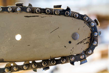 Closeup view of a chainsaw bar and cutting chain.