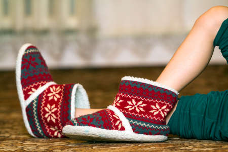 Bare child legs and feet in red winter christmas boots with ornament pattern
