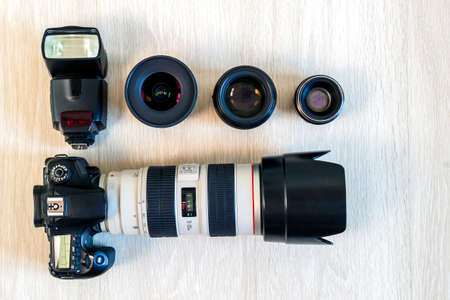Top view of photo DSLR camera, camera lenses and a flash