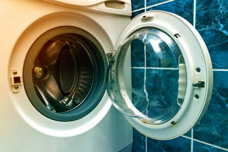 A close up of open washing machine in bathroom