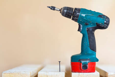 Electric cordless screwdriver and one screw close-up Stock Photo