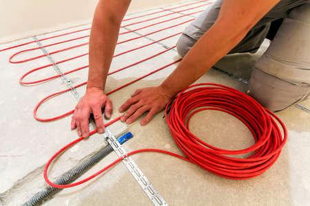Der Tauber do ob de Rothenburg, Alemanha - 12 de novembro de 2017: Trabalhador que instala o cabo de aquecimento para o assoalho morno. Obras de renovação Foto de archivo - 93366395